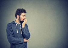 Preoccupied anxious man biting his fingernails. Preoccupied anxious young man biting his fingernails feeling insecure and worried royalty free stock images
