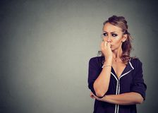 Preoccupied anxious woman biting her fingernails looking to the side. Preoccupied anxious young woman biting her fingernails looking to the side royalty free stock image