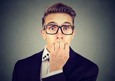 Preoccupied anxious young business man in glasses biting his fingernails looking at camera royalty free stock photos