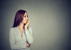 Preoccupied anxious young woman biting fingernails Stock Image