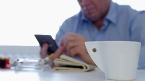 Preoccupied Businessman Smoke a Cigarette Drink Coffee and Text Using Mobile stock footage