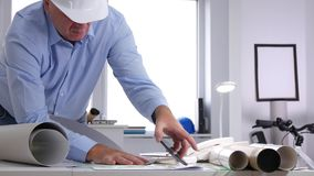 Preoccupied engineer open and analyze a technical plan in office.  stock footage