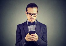 Preoccupied sad man thinking what to reply to received text message on cell phone. Isolated on gray wall background royalty free stock photography