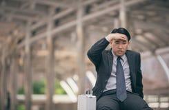 A preocupação triste dos homens de negócios cansado senta-se com o saco preto na rua fotografia de stock