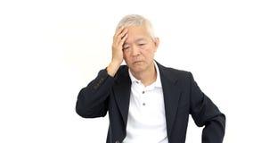 Preocupación y tensión mayores asiáticas del hombre de negocios imagen de archivo