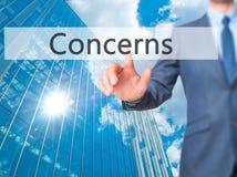 Preocupaciones - botón del tacto de la mano del hombre de negocios en la pantalla virtual internacional Foto de archivo libre de regalías