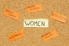 Preocupaciones de la salud de las mujeres en una tarjeta del corcho Foto de archivo libre de regalías