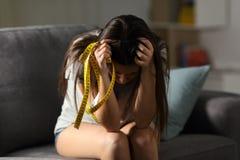Preocupante adolescente triste sobre el aspecto que sostiene una cinta de la medida Foto de archivo