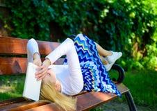 Prepárese para la rotura cansada mujer de la toma de la cara de la prueba que se relaja en libro de lectura del jardín El estudia imágenes de archivo libres de regalías