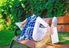 Prepárese para la rotura cansada mujer de la toma de la cara de la prueba que se relaja en libro de lectura del jardín El estudia imagen de archivo