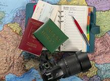 Preparándose para el viaje, viaje En el mapa es un pasaporte, un boleto, una tarjeta de prensa, un cuaderno y una cámara imagen de archivo libre de regalías
