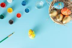 Prepar?ndose para Pascua, la cesta con los huevos de Pascua hechos a mano al lado de las pinturas multicoloras y el cepillo en un imagenes de archivo