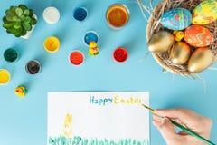Preparándose para Pascua, la cesta con los huevos de Pascua hechos a mano al lado de las pinturas y de la mano multicoloras con e imagen de archivo
