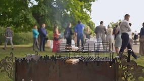 Preparação da carne de porco e do assado fritados para os convidados da cerimônia de casamento no ar livre Soldador com carvões vídeos de arquivo