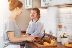 A preparação da mãe do café da manhã da família e da filha da criança cortou b Fotografia de Stock