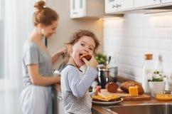 A preparação da mãe do café da manhã da família e a filha da criança cozinham foto de stock