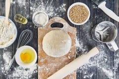 Preparação da massa para o pão, pizza, configuração lisa do alimento na mesa de cozinha Trabalhando com farinha, ovos, passas, se Fotografia de Stock Royalty Free