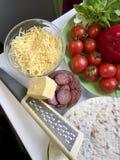 Preparação da pizza Os ingredientes necessários estão na tabela: queijo, salsicha, base da pizza e vegetais fotografia de stock royalty free