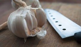 Preparação de alimento biológico, cozinhando o conceito: cabeças cruas dos bulbos do alho, faca em um fundo de madeira rústico da Foto de Stock