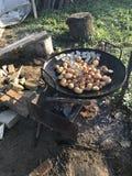 Preparação de batatas cozidas com bacon As batatas e a banha estão na grade O fogo está queimando-se, os carvões está ardendo sem fotografia de stock royalty free