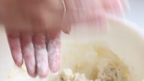 Preparação de bolos do queijo Uma mulher rola e forma uma massa No recipiente é o requeijão e um ovo da galinha é batido para for filme