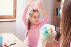 Preparação de easter da mãe e da filha junto em casa nas orelhas do coelho fotografia de stock royalty free