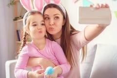 A preparação de easter da mãe e da filha junto em casa nas orelhas do coelho que tomam fotos do selfie faz caretas fotos de stock