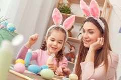 Preparação de easter da mãe e da filha junto em casa que senta-se nas orelhas do coelho que discutem o projeto imagem de stock royalty free