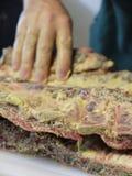 Preparação de reforços de carne de porco através da mostarda que espalha com mãos Imagens de Stock