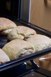 Preparação de rolos de canela A folha de cozimento retirada do forno Há bolos prontos e um rolo com canela nela Fotos de Stock Royalty Free