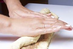 Preparação de rolos de canela A mulher desliga a massa com um enchimento da canela e do açúcar Fotos de Stock Royalty Free