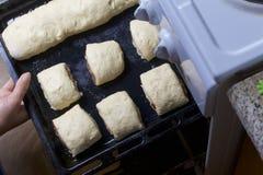Preparação de rolos de canela A mulher envia aos boletos do forno dos rolos e dos rolos com canela, colocados em uma bandeja do c Imagens de Stock