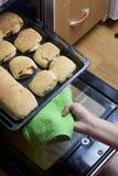 Preparação de rolos de canela A mulher toma uma folha de cozimento fora do forno Há bolos prontos e um rolo com canela nela Imagem de Stock