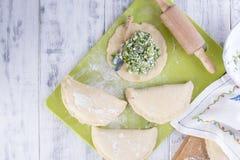 Preparação de tortas caseiros com ervas e queijo frescos dough Um pino do rolo e uma toalha com um teste padrão Espaço livre para imagens de stock royalty free