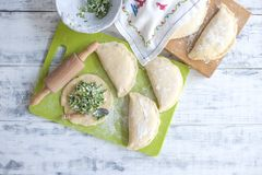 Preparação de tortas caseiros com ervas e queijo frescos dough Um pino do rolo e uma toalha com um teste padrão Espaço livre para fotos de stock royalty free