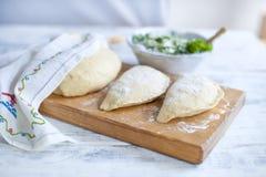 Preparação de tortas caseiros com ervas e queijo frescos dough Um pino do rolo e uma toalha com um teste padrão Espaço livre para fotografia de stock