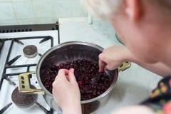 Preparação do bolo com cerejas e framboesas. Fotos de Stock