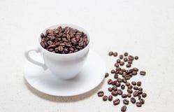 Preparação do café Feijões de café em um copo branco foto de stock royalty free