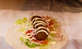 Preparação do falafel com os vegetais na rua justa fotos de stock royalty free