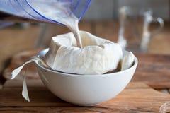Preparação do leite da semente de papoila - esticando o leite através de um saco do leite fotografia de stock royalty free