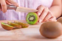 Preparação dos alimentos da mulher - cortando um fruto de quivi Imagens de Stock Royalty Free