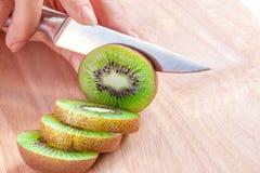 Preparação dos alimentos da mulher - cortando um fruto de quivi Imagem de Stock Royalty Free