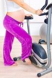 Preparação grávida para o exercício na bicicleta. Close up imagens de stock
