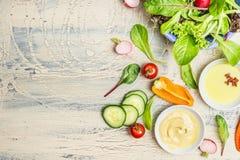 Preparação orgânica fresca da salada verde com os ingredientes do óleo e do molho no fundo rústico claro, vista superior, lugar p Fotos de Stock