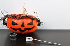 Preparação para Dia das Bruxas: abóbora alaranjada pintada com pintura preta e uma escova Closup Conceito da decoração do feriado imagem de stock