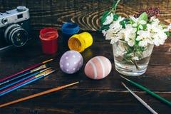 Preparação para Easter Ovos da páscoa feitos a mão coloridos pintados, pinturas, escovas, câmera retro e vaso com flores em um CC Imagem de Stock Royalty Free
