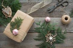 Preparação para o feriado do Natal Do Natal a vida ainda do giftbox, decoração, guita, árvore de abeto, galhos, vintage scissors Fotos de Stock