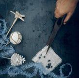 Preparação para o feriado - entregue com as decorações velhas do Natal das tesouras - laço, estrela, bola, colisão Vista superior Fotos de Stock