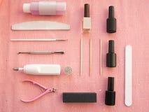 A preparação para o tratamento de mãos ou o pedicure com verniz para as unhas do gel ajustaram-se no fundo cor-de-rosa, vista sup imagens de stock royalty free