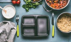 Preparação saudável da lancheira com quinoa, molho dos feijões dos tomates no fundo da mesa de cozinha com cutelaria Foto de Stock